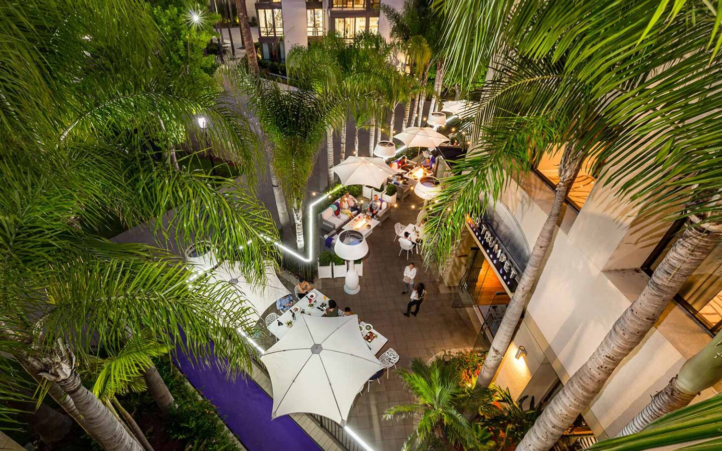 outdoor dining patio at Silver Trumpet Restaurant under umbrellas and trees