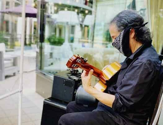 man playing guitar on outdoor chair with bandana facemask